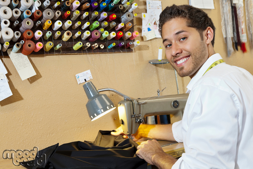 Portrait of young tailor sewing cloth in shop