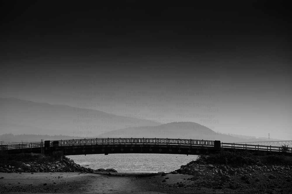 A silhouette of a bridge in Stanley Park leading to Dead Man's Island.
