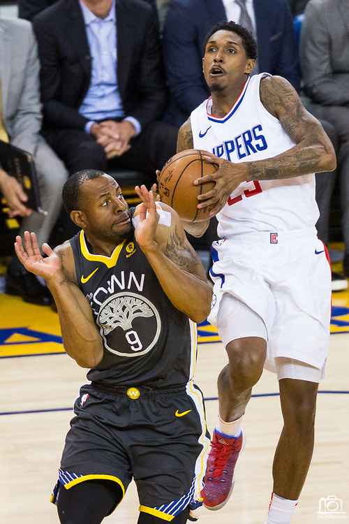 Golden State Warriors forward Andre Iguodala (9) reacts to LA Clippers guard Lou Williams (23) taking the ball to the basket at Oracle Arena in Oakland, California, on February 22, 2018. (Stan Olszewski/Special to S.F. Examiner)