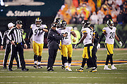 NFL umpire Mark Pellis (131) looks on as a Pittsburgh Steelers coach restrains Pittsburgh Steelers outside linebacker James Harrison (92) as he helps to regain order and clear the field of unnecessary players and coaches after Cincinnati Bengals running back Giovani Bernard (25) gets hit hard by Pittsburgh Steelers inside linebacker Ryan Shazier (50) causing a third quarter fumble, recovered by Shazier, and starting a player melee over no penalty call for unnecessary roughness and leading with the helmet during the NFL AFC Wild Card playoff football game against the Pittsburgh Steelers on Saturday, Jan. 9, 2016 in Cincinnati. The Steelers won the game 18-16. (©Paul Anthony Spinelli)