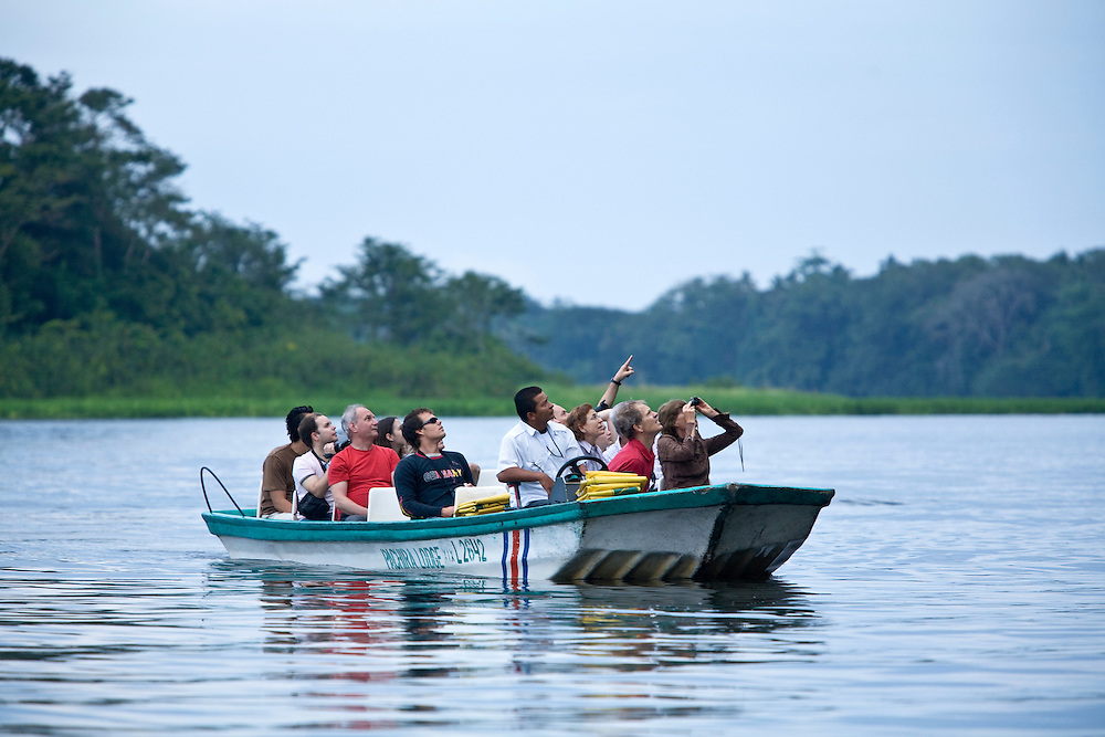 Tourists take an early morning tour of Tortuguero National Park in Costa Rica. Located on the Caribbean coast, Tortuguero is well known for the nesting turtles on its beaches as well as its diverse wildlife along its rivers banks.