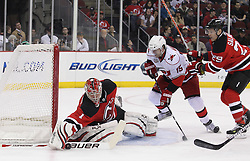 Feb 16; Newark, NJ, USA; New Jersey Devils goalie Johan Hedberg (1) makes a save while Carolina Hurricanes center Tuomo Ruutu (15) looks for the rebound during the first period at the Prudential Center.