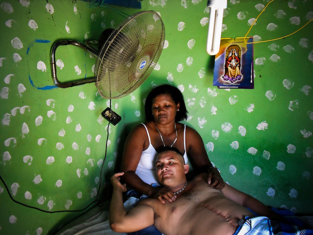 """Jesus Guevara, 33, visits with his girlfriend, Claudia Brito, 45, during a congeal visit day, at San Antonio prison in Porlamar, Venezuela in a private room that he rents from the prison """"prawn"""" (leader) convicted drug trafficker, Teófilo Rodríguez. The prison in Porlamar on Margarita Island houses 2,000 inmates, and is known amongst criminals as the prime place to serve time. During his reign at the prison, Rodríguez has constructed four swimming pools, a cockfighting arena, hosts hip hop concerts and dances at the prison discothèque, and has built over 200 private rooms where prisoners may enjoy conjugal visits three times a week."""