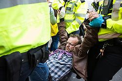 London, UK. 18th April 2019. Police officers arrest a climate change activists from Extinction Rebellion as part of a large police operation to try to clear Oxford Circus of protesters on the fourth day of the International Rebellion to call on the British government to take urgent action to combat climate change.