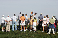 2006:  Stock Golf course detail, graphic, product, grass, sky, ball, fans, gallery, people, color. Gallery of fans watch a golfer tee off.