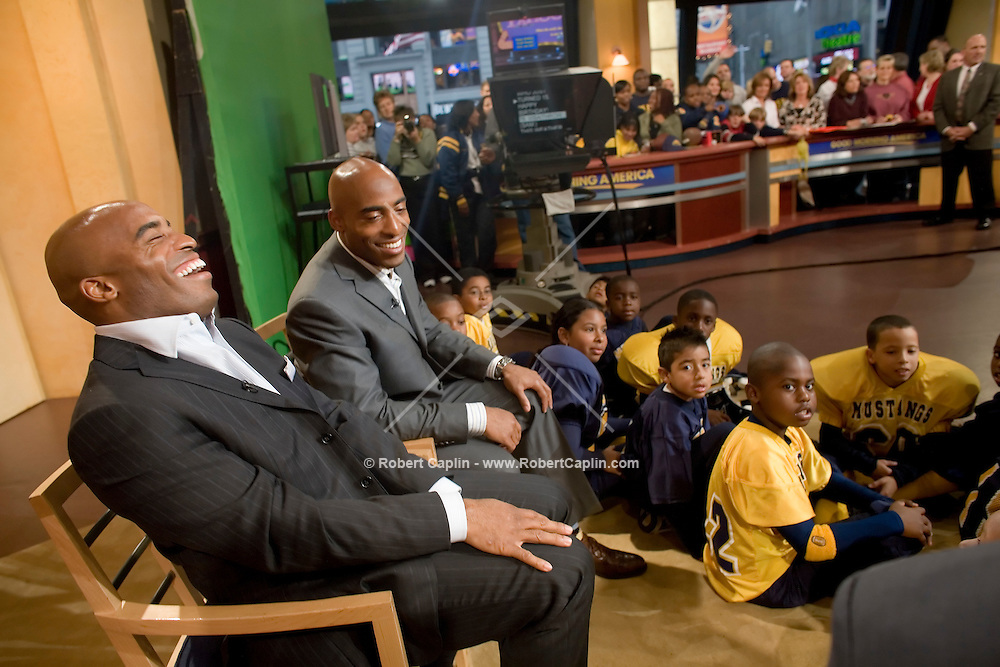 "Professional football players and identical twin brothers, Tiki, left, and Ronde Barber, right, make an appearance on Good Morning America where they were tackled by a youth football team. The Barbers made appearences on FOX News, ESPN2, Good Morning America, and a book signing at Barns and Noble in New York while promoting their third children's book titled ""Teammates"".  Tues. Oct. 17, 2006."