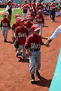 ANAHEIM, CA - APRIL 26:  A young baseball player gets a low five during a walk around the field at Little League Days prior to the Los Angeles Angels of Anaheim game against the Seattle Mariners at Angel Stadium on Sunday, April 26, 2009 in Anaheim, California.  The Angels shut out the Mariners 8-0.  (Photo by Paul Spinelli/MLB Photos via Getty Images)