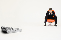 Wad of cash on mouse trap with worried businessman sitting on chair representing financial difficulties
