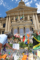 Executive Mayor of Cape Town, Mrs Patricia De Lille, reads some of the condolence messages on some of the numerous bunches of flowers during a time of national mourning the death of the first democratically elected president, Nelson Mandela, in front of the Cape Town City Hall, South Africa, Saturday, 7th December 2013. Picture by Roger Sedres / i-Images