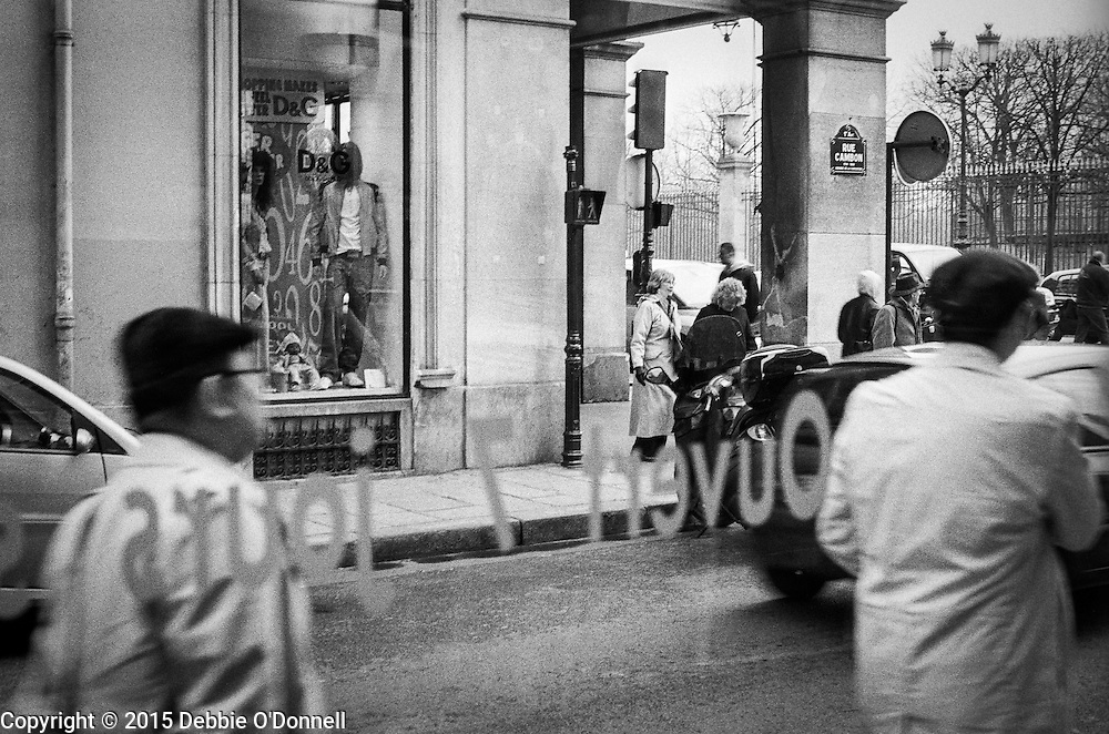 Two men wearing identical berets and coats walk by a window along Rue Cambon, Paris.