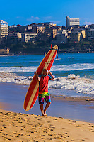 Surfer carrying a long board, Manly Beach, Sydney, New South Wales, Australia.