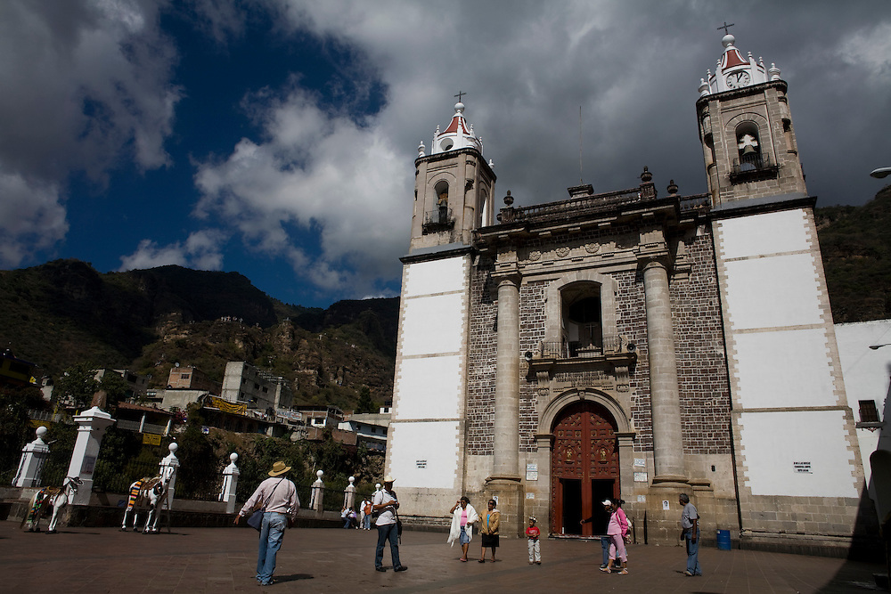 People walk in front of the church in Chalma.  Chalma is the second most important pilgrimage site in Mexico.  People come from all over the country to visit the Senor de Chalma. They often arrive wearing crowns made of flowers, and leave the crowns at the church.