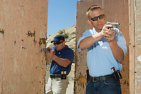 Two men aiming hand guns at firing range