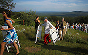 Guests carry up their chairs after the ceremony including, center, Kevin McNiff of San Francisco, at Novelist and writer Joyce Maynard and Jim Barringer's wedding in Harrisville, N.H., Saturday, July 6, 2013.  (Cheryl Senter for the New York Times)