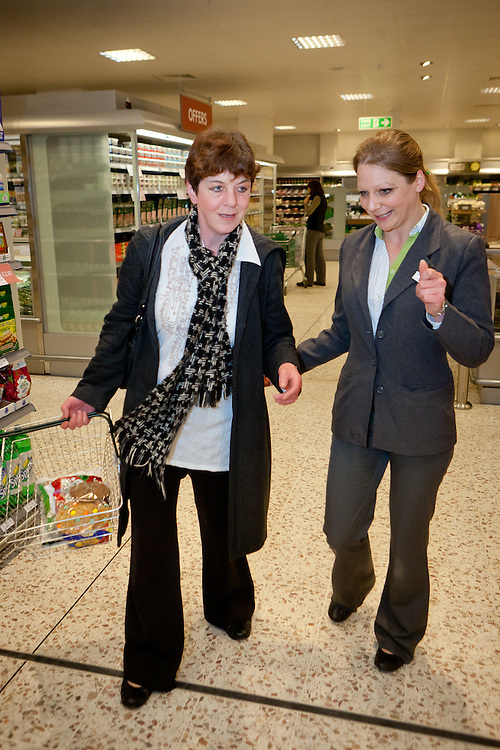 Trish Demirasal shows customer Cathy Hinley the whereabouts of a product