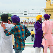 People at Harmandir Sahib, the Golden Temple, and by its sacred pool.
