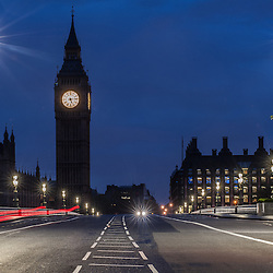 Empty Westminster Bridge in London with a car passing by under the Big Ben Tower