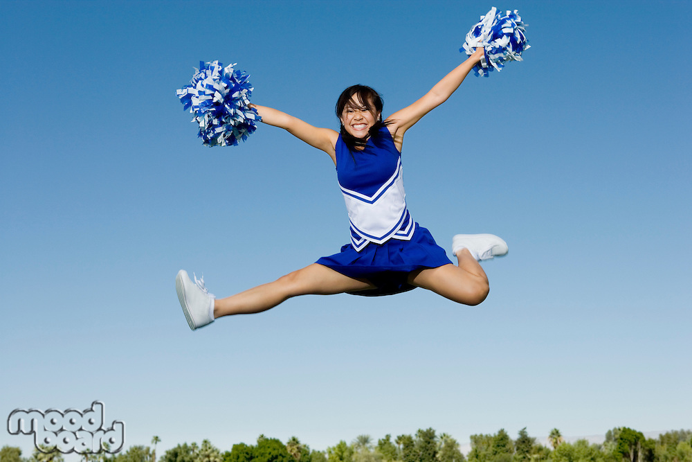 Jumping Cheerleader Performing Cheer in Mid-Air