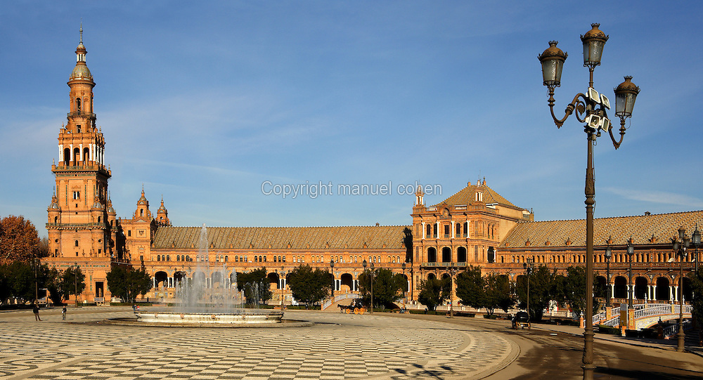 Low angle view of Plaza de Espana, Seville, Spain, pictured on January 4, 2007, in the morning. Built in the Maria Luisa Park for the  Ibero-American Exposition of 1929, this huge semi-circular building, designed by Anibal Gonzalez, is a good example of Sevillian Regionalism, a combination of  Neo-Mudejar and Art Deco styles. There is a tower at each end, and a fountain in the centre of the semi-circle. Picture by Manuel Cohen.