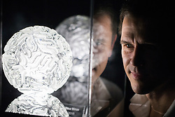 © London News Pictures. 03/02/2017. Luke Jerram with his Zika virus glass sculpture. Luke Jerram's Glass Microbiology exhibition on display at At-Bristol. The exhibition showcases eight jewel-like sculptures, showing accurate representations of deadly viruses and microbiology. Photo credit: Brad Wakefield/LNP
