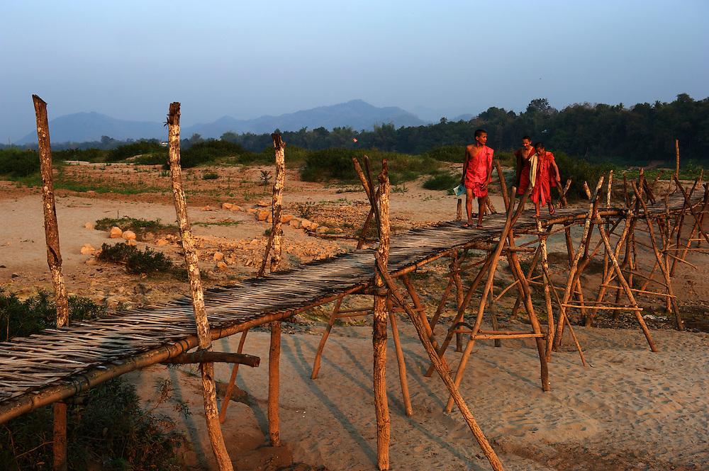 Novice monks cross the sandbanks of the Mekong River during the dry season using bamboo bridges.