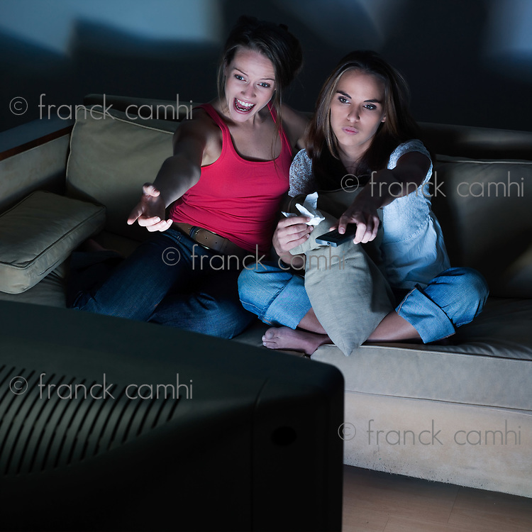 pictures in a living room of two young girls sitting on a couch watching on tv
