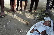 A crowd gathers around the body of a small child evidently killed (a pink ribbon was knotted tightly around the child's throat) and dumped by the roadside in Port-au-Prince, Haiti, May 1995. (Photo by Roger M. Richards)