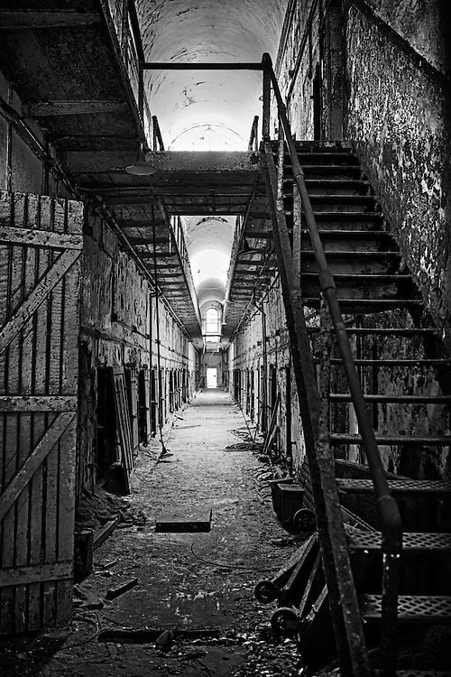 Photographer Dan Komoda's image in black and white of the interior of the Eastern State Penitentiary showing a staircase and cell blocks.