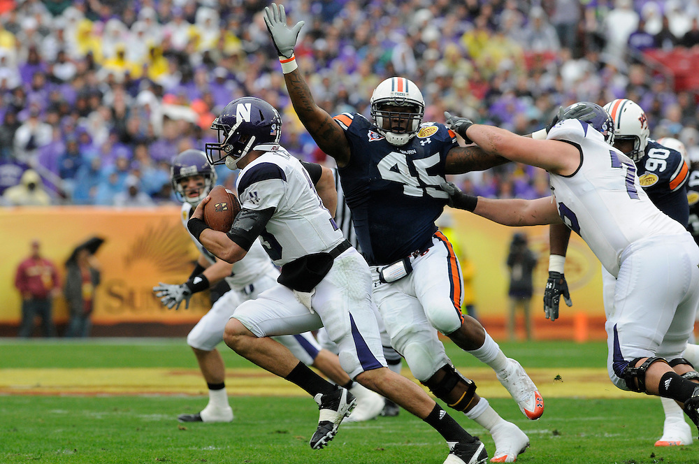 January 1, 2010: Defensive end Antoine Carter of the Auburn Tigers pressures quarterback Mike Kafka of the Northwestern Wildcats during the NCAA football game between the Northwestern Wildcats and the Auburn Tigers in the Outback Bowl. The Tigers were leading the Wildcats 21-7 at halftime.