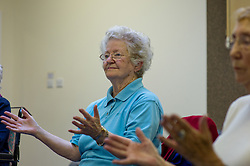 People enjoy socialising and activity at a council run over 50's club in Basildon, Essex. Members participating in a sit down exercise class. *Model Released*