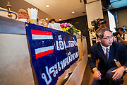 15 DECEMBER 2013 - BANGKOK, THAILAND: A man puts up an unauthorized banner that was ordered removed by Tongthong Chandrangsu, permanent secretary of the Prime Minister's Office, and moderator of the forum during a forum on political reform in Thailand at the Queen Sirikit National Convention Center. The forum was organized by Thai Prime Minister Yingluck Shinawatra.      PHOTO BY JACK KURTZ