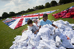 © licensed to London News Pictures. London, UK 09/08/2012. Children playing with unwanted items of clothing donated to the Shwopping initiative. M&S, local volunteers and Oxfam made the world's largest Union Jack flag clothes mosaic in West Ham Park, East London. All items used in the creation of the flag will be reused, resold or recycled by Oxfam. The campaign aims to put an end to the one billion items currently ending up in landfill every year. Photo credit: Tolga Akmen/LNP