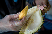 A customer picks up a durian of the Red Prawn variety using a plastic glove at Durian Kaki, a roadside fruit stall owned by Tan Eow Chong and his family in Bayan Lepas, Pulau Pinang, Malaysia on Sunday, June 16th, 2019. China has been opening up its market to many other varieties of durian despite the Musang King variety still holding the highest, most coveted position.   Photo by Suzanne Lee/PANOS for Los Angeles Times