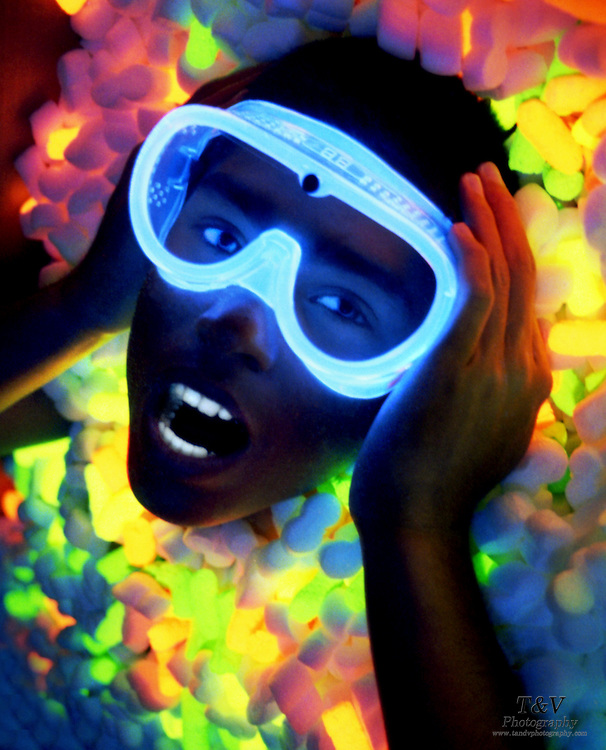 A young man wearing glowing safety goggles grabs his face with his hands in a bed of glowing packing peanuts.Black light