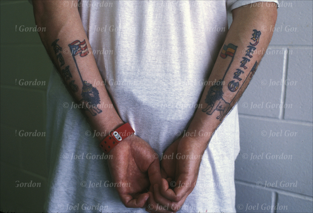 Hispanic American inmate in jail, close-up with hands behind his back of gang-identifying tattoos, Latin Kings, hit man, Tag: King Yellow, Orange County Jail, FL