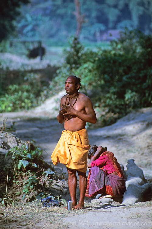 Asia, Nepal, Bardia. A local Tharu man praying before bathing in river.