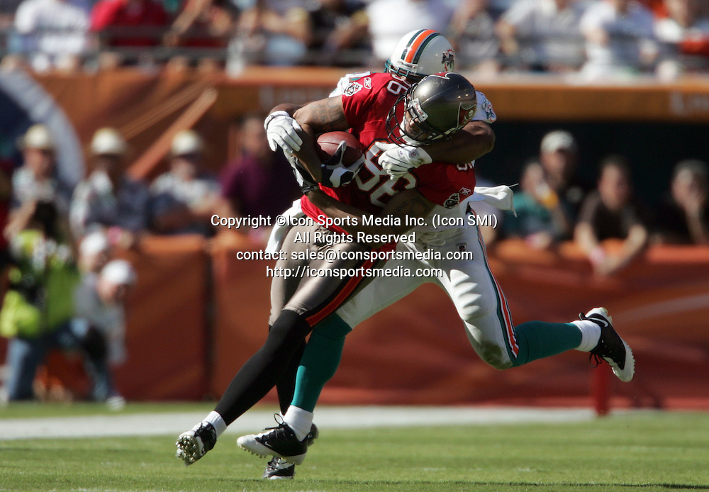 15 NOV 2009:  Jerramy Stevens (86) of the Buccaneers attempts to get additional yardage as Akin Ayodele (51) of the Dolphins hangs on during the game between the Tampa Bay Buccaneers and the Miami Dolphins at Landshark Stadium in Miami Gardens, FL.  The Dolphins defeated the Buccaneers by the score of 25 to 23.