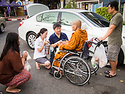 "14 FEBRUARY 2014 - BANGKOK, THAILAND: People present alms to an elderly monk on Makha Bucha Day at Wat That Thong (also called Wat Tad Tong) in Bangkok. The aims of Makha Bucha Day are: not to commit any kind of sins, do only good and purify one's mind. It is a public holiday in Cambodia, Laos, Myanmar and Thailand. Many people go to the temple to perform merit-making activities on Makha Bucha Day. The day marks four important events in Buddhism, which happened nine months after the Enlightenment of the Buddha in northern India; 1,250 disciples came to see the Buddha that evening without being summoned, all of them were Arhantas, Enlightened Ones, and all were ordained by the Buddha himself. The Buddha gave those Arhantas the principles of Buddhism, called ""The ovadhapatimokha"". Those principles are:  1) To cease from all evil, 2) To do what is good, 3) To cleanse one's mind. The Buddha delivered an important sermon on that day which laid down the principles of the Buddhist teachings. In Thailand, this teaching has been dubbed the ""Heart of Buddhism.""   PHOTO BY JACK KURTZ"