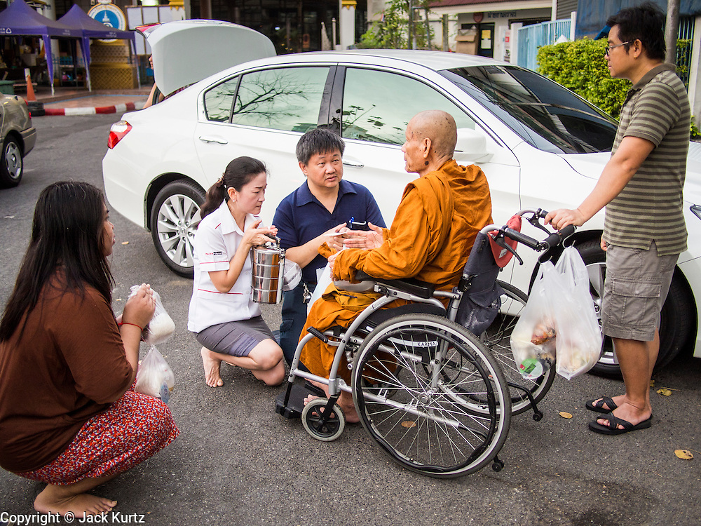 """14 FEBRUARY 2014 - BANGKOK, THAILAND: People present alms to an elderly monk on Makha Bucha Day at Wat That Thong (also called Wat Tad Tong) in Bangkok. The aims of Makha Bucha Day are: not to commit any kind of sins, do only good and purify one's mind. It is a public holiday in Cambodia, Laos, Myanmar and Thailand. Many people go to the temple to perform merit-making activities on Makha Bucha Day. The day marks four important events in Buddhism, which happened nine months after the Enlightenment of the Buddha in northern India; 1,250 disciples came to see the Buddha that evening without being summoned, all of them were Arhantas, Enlightened Ones, and all were ordained by the Buddha himself. The Buddha gave those Arhantas the principles of Buddhism, called """"The ovadhapatimokha"""". Those principles are:  1) To cease from all evil, 2) To do what is good, 3) To cleanse one's mind. The Buddha delivered an important sermon on that day which laid down the principles of the Buddhist teachings. In Thailand, this teaching has been dubbed the """"Heart of Buddhism.""""   PHOTO BY JACK KURTZ"""