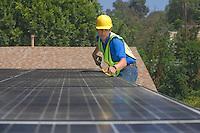 Maintenance worker measures solar array on rooftop Los Angeles California