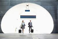 Businessman and businesswoman rushing in railroad station