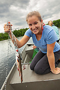 A young woman shows off a Rainbow Trout caught in Trout Lake in the Northwoods village of Boulder Junction, Wisconsin.