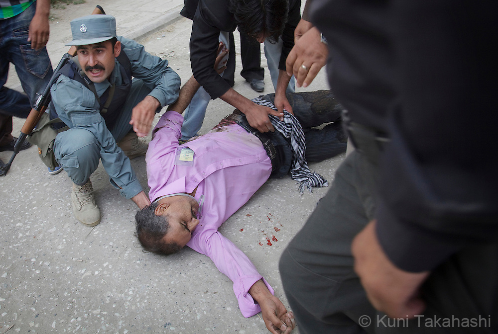A police officer attends an injured journalist who was shot in hip during multiple insurgent attacks in Kabul, Afghanistan on Sep 13, 2011. Terrorists attacked multiple locations including U.S. Embassy and a nearby NATO base in Kabul..(Photo by Kuni Takahashi) .
