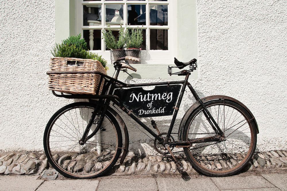 Old fashioned bicycle with basket sits outside shop in Dunkeld, Scotland