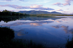Clouds reflect in Cherry Pond.  Pondicherry National Wildlife Refuge.  White Mountains - Pliny Range is in the distance.  National Natural Landmark. Jefferson, NH