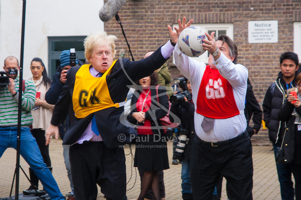 Ealing, London, December 9th 2014. Mayor of London Boris Johnson visits Ealing, Hammersmith and Fulham College accompanied by   Deputy Mayor for Policing and Crime Stephen Greenhalgh to launch a new initiative to increase black and ethnic minority applicants to the Met. PICTURED: Boris Johnson and Stephen Greenhalgh grapple for the ball during a game of netball.