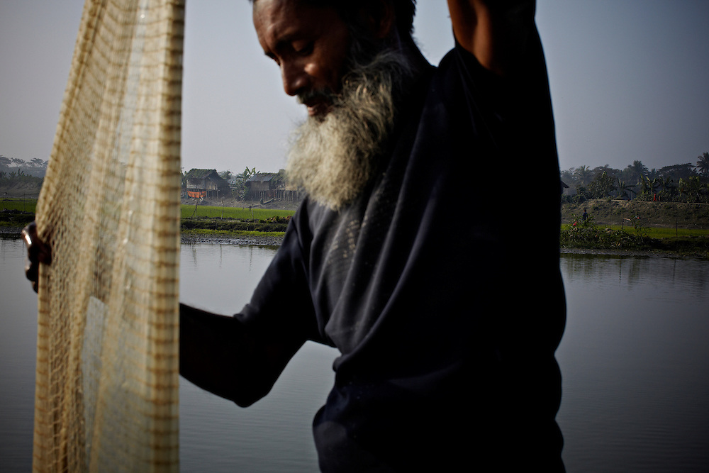 Taher Hussein. in september 2008 he had to move to the second floor of his house due to heavy flooding. in the background is the embankment.. ?This area in the south of Bangladesh has been called ground zero of climate-change due to heavy river and ocean erosion. The lowlying area is also hugely affected by cyclones and rising sea-levels...By the Mouth of Ganges, at the Bay of Bengal is the Island of Bhola. This home of about two million people is considered to be ground zero of climate change. Half the island has disappeared in the past 40 years, and according to scientists the pace is not going to slow down. People pack up and leave as the water get closer. Some to a nearby embankment, while those with enough money move further inland, but for most life move on until the inevitable. It's always about survival for the people in one of the worlds poorest countries...Photo by: Eivind H. Natvig/MOMENT