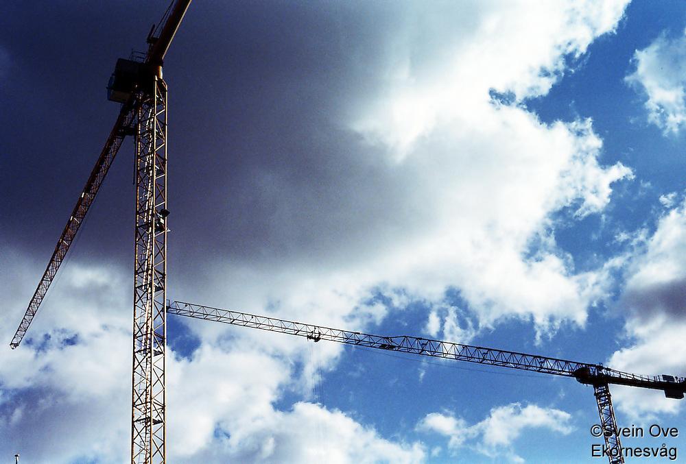 Berlin februar 2012.<br /> To heisekraner ved en byggeplass i Berlin. I bakgrunnen er det blå himmel og mørke skyer.<br /> Foto: Svein Ove Ekornesvåg