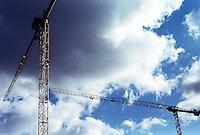 Berlin februar 2012.<br /> To heisekraner ved en byggeplass i Berlin. I bakgrunnen er det bl&aring; himmel og m&oslash;rke skyer.<br /> Foto: Svein Ove Ekornesv&aring;g