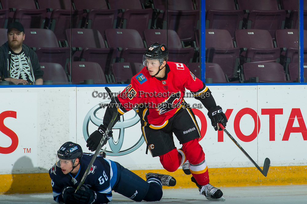 PENTICTON, CANADA - SEPTEMBER 11: Zach Fischer,  #48 of Calgary Flames checks Jansen Harkins #58 of Winnipeg Jets to the ice on September 11, 2017 at the South Okanagan Event Centre in Penticton, British Columbia, Canada.  (Photo by Marissa Baecker/Shoot the Breeze)  *** Local Caption ***